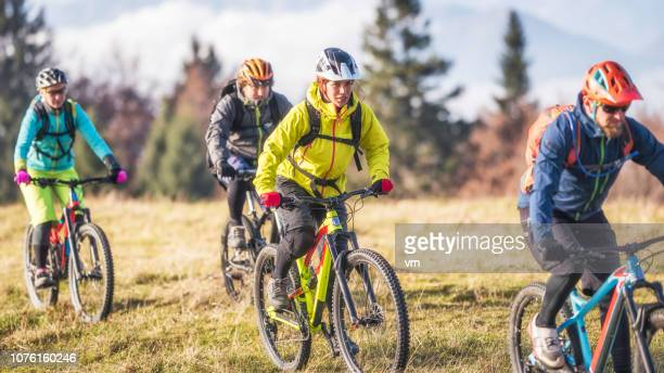front view of four friends mountain biking - cross country cycling stock pictures, royalty-free photos & images