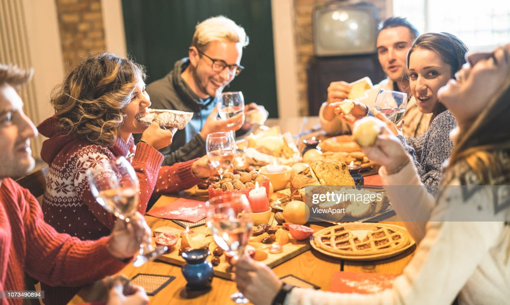 Front view of friends group tasting christmas sweets food and having fun at home drinking champagne sparkling wine - Winter holidays concept with people enjoying time eating together - Warm filter : Stock Photo