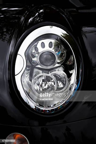 Front view of Headlight of black Morgan car, copy space