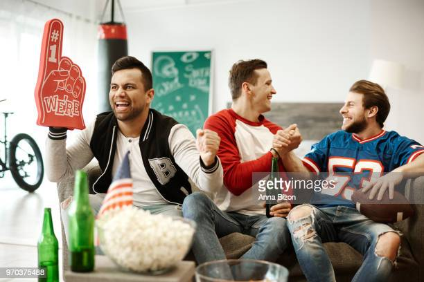 front view of loyal, confident football fans. debica, poland - foam finger stock photos and pictures