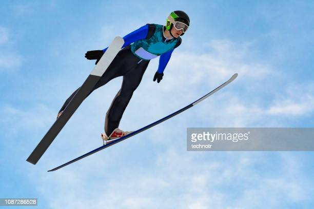 front view of male ski jumper in mid-air against the blue sky - ski jumping stock pictures, royalty-free photos & images