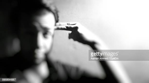 Front View Of Man Pointing At Head Against Wall