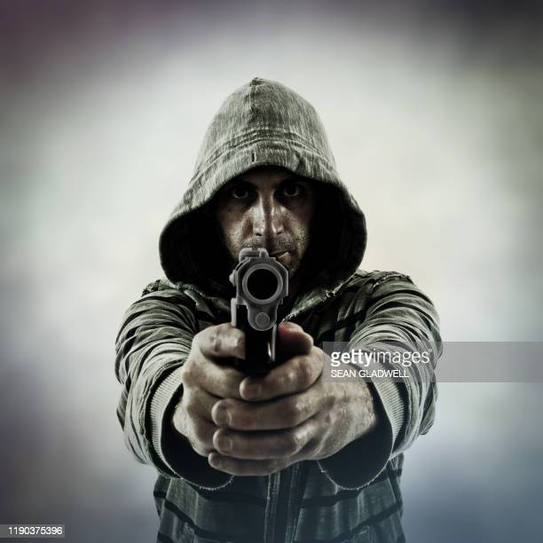 front view of man pointing gun - gunman stock pictures, royalty-free photos & images