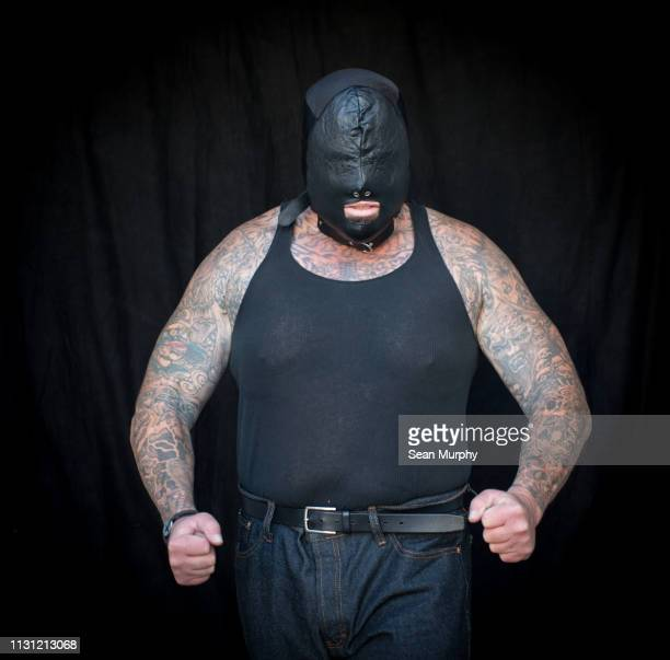 front view of mature tattooed man wearing vest and face mask - macho stock pictures, royalty-free photos & images
