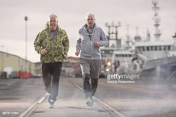 Front view of men jogging on docklands