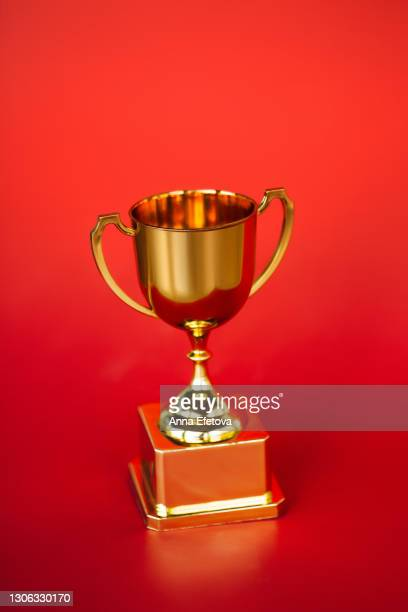 front view of metallic golden goblet on bright red background. goal achievement concept - championship stock pictures, royalty-free photos & images