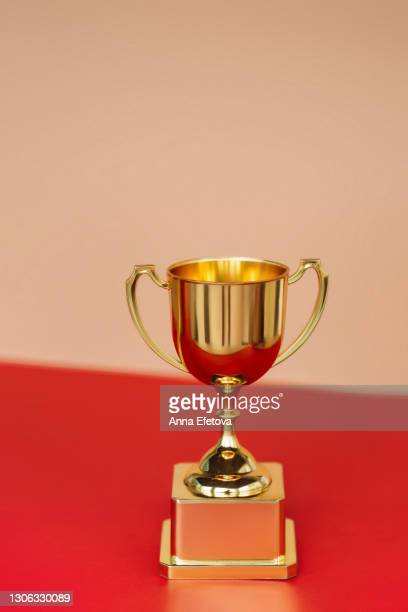 front view of metallic golden goblet on red table near beige wall. goal achievement concept - championship stock pictures, royalty-free photos & images