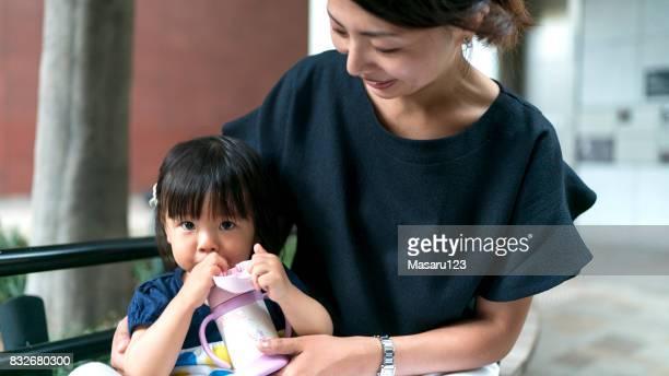 水を飲む母と赤ちゃんの女の子の正面図