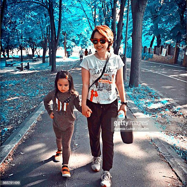 Front View Of Mother And Daughter Walking On Footpath In Park