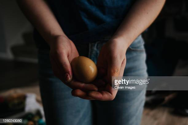 front view of older girl holding a yellow dyed chicken egg - dirty easter stock pictures, royalty-free photos & images