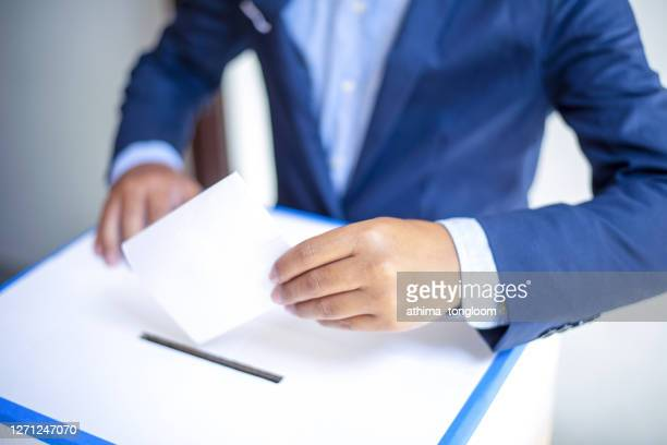 front view of person holding ballot paper casting vote at a polling station for election vote. - governor stock pictures, royalty-free photos & images