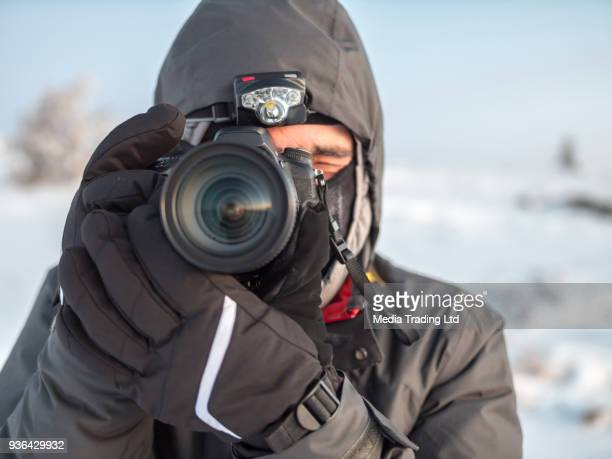front view of professional photographer pointing his digital camera forward - strap stock photos and pictures