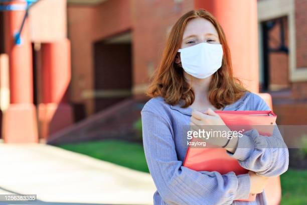 front view of red-headed teen wearing mask on campus - new normal concept stock pictures, royalty-free photos & images