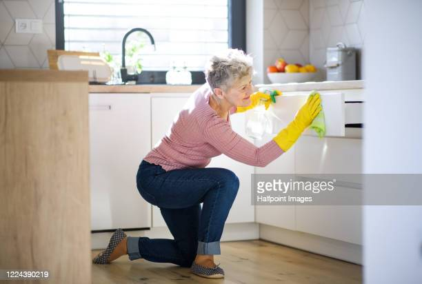 front view of senior woman indoors at home, cleaning kitchen. - disruptaging foto e immagini stock
