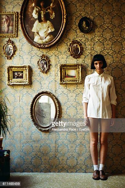 Front View Of Serious Woman Standing By Picture Frames On Wall