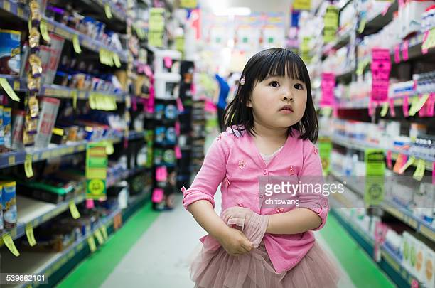 Front view of small girl walking alone between stalls in supermarket