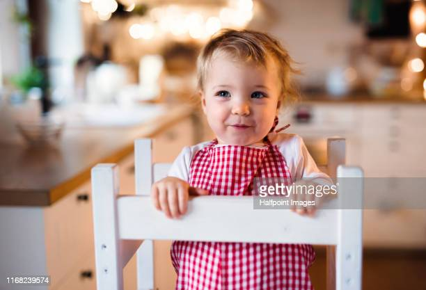 a front view of small toddler girl indoors, looking at camera. - tower stock pictures, royalty-free photos & images
