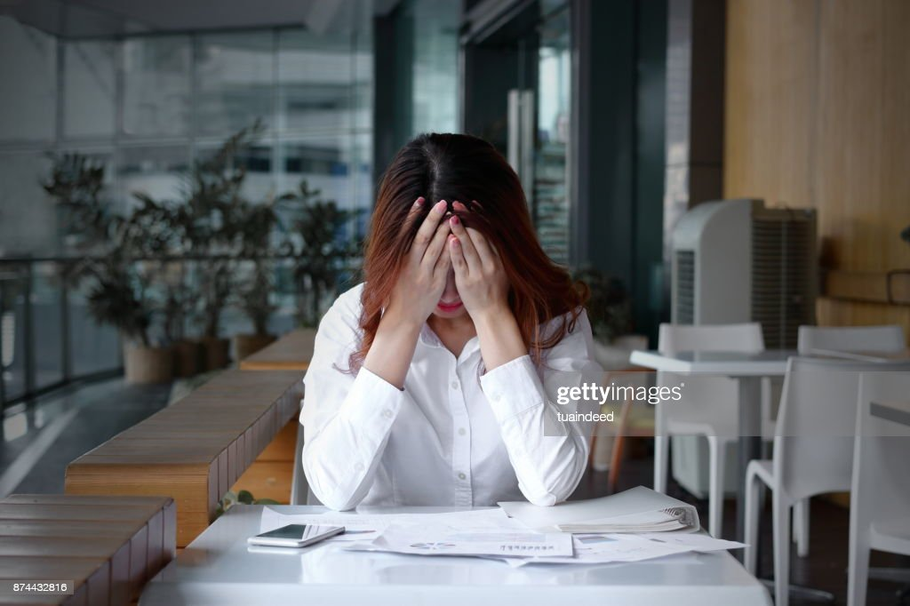 Front view of stressed frustrated young Asian business woman covering face with hands on the desk in office : Stock Photo