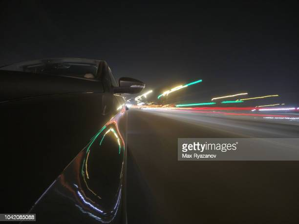 front view of the car while driving in the city at night. shooting at long exposure. light traces of illumination of buildings and road - movendo um veículo - fotografias e filmes do acervo