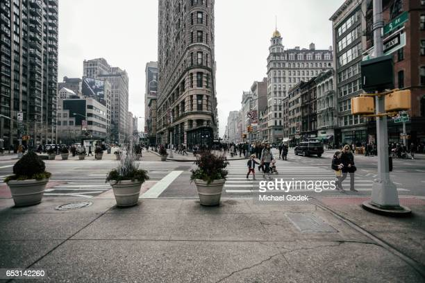 Front view of the Flatiron building with pedestrians walking across the crosswalk