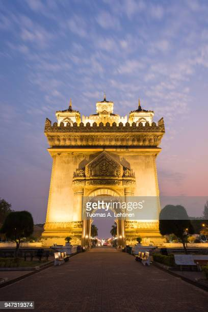 Front view of the lit Patuxai (Victory Gate or Gate of Triumph) war monument in Vientiane, Laos, at dusk.