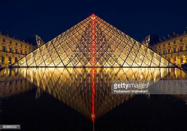 Front view of The Louvre museum with reflection at dusk.