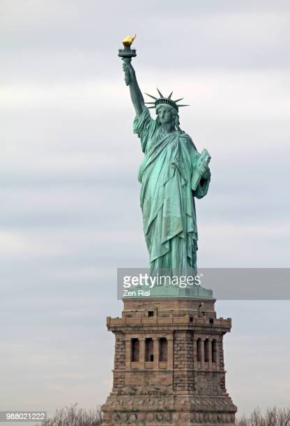 front view of the statue of liberty on liberty island in new york harbor, new york city - statue of liberty stock pictures, royalty-free photos & images