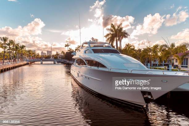 front view of the sun coming down at sunset in fort lauderdale canals. luxury yachts in las olas boulevard, florida, usa - yacht foto e immagini stock