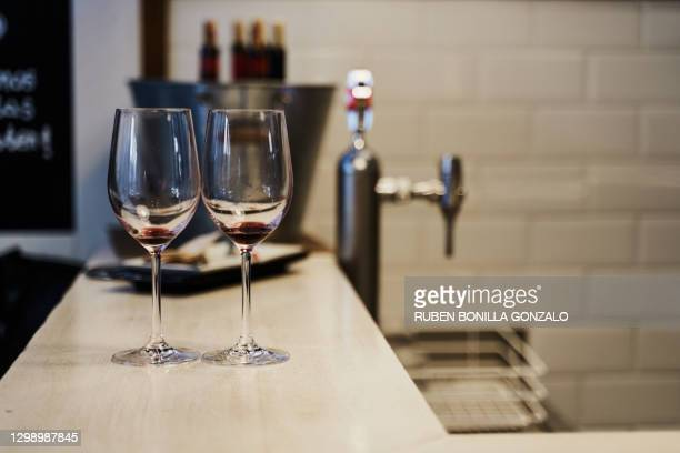 front view of two empty crystal wine glasses on a bar table with a metallic bucket with some opened wine bottles with cork and a beer faucet without jar at the back. horizontal photography. - cleaning after party stock pictures, royalty-free photos & images