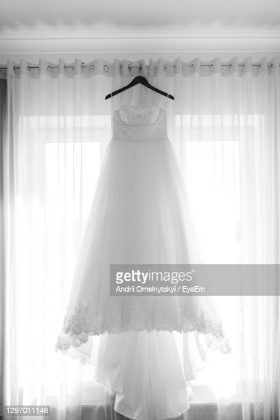 front view of wedding dress hanging against white curtain - dress stock pictures, royalty-free photos & images