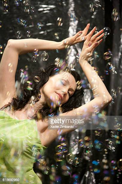 Front view of woman dancing and relaxing wearing green dress drenched in shower of soap bubbles on April 18 2008 in Moscow Russia