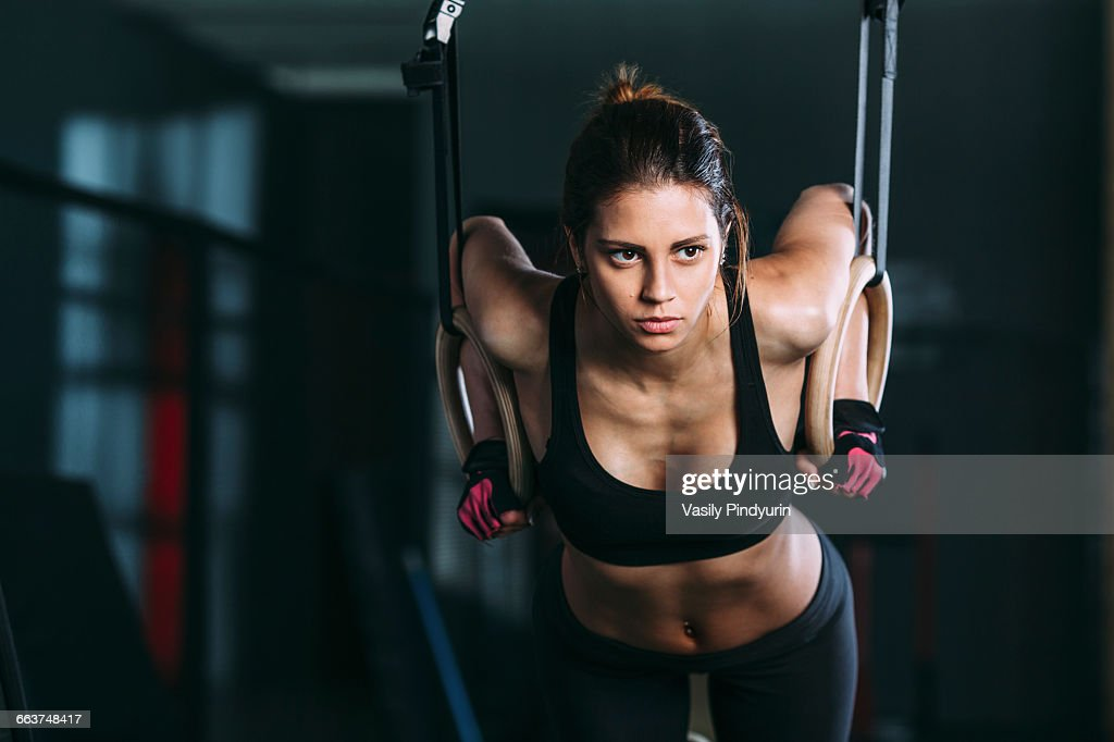 Front view of woman hanging on gymnastic rings at gym : Stock Photo