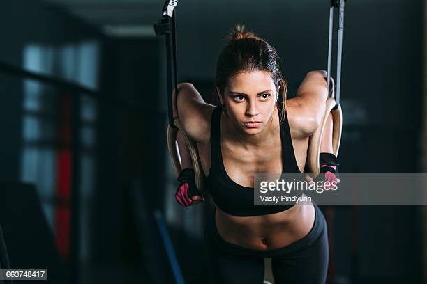 Front view of woman hanging on gymnastic rings at gym