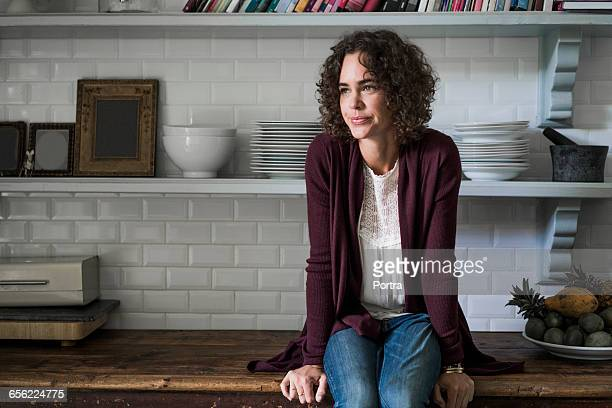 front view of woman sitting on kitchen counter - cardigan photos et images de collection