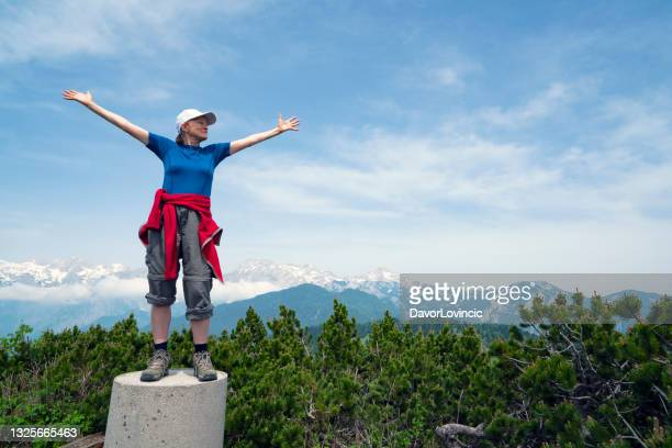 front view of  woman, standing on pillar with extended arms on the top of land - moment of silence stock pictures, royalty-free photos & images