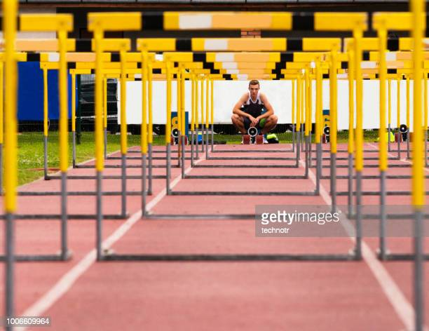 front view of young athlete through the hurdles - hurdling stock photos and pictures