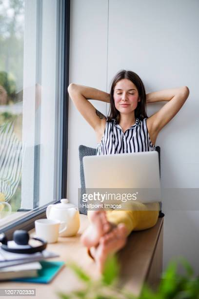 front view of young female student with sitting by window at home. - 18 19 years stock pictures, royalty-free photos & images