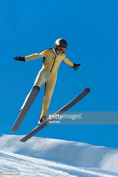 Front View of Young Male Ski Jumper Landing at 30m