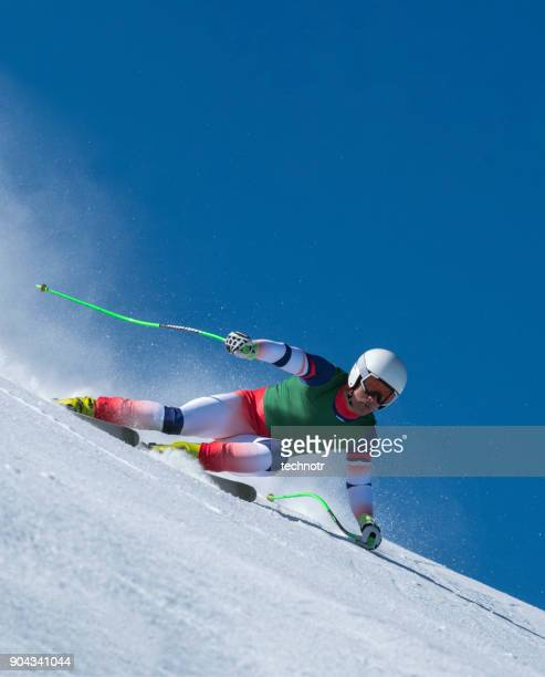 Front View of Young Male Skier at Downhill Ski Training Against the Blue Sky