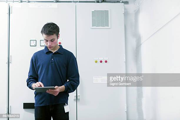 front view of young man in switchgear control room using digital tablet looking down - sigrid gombert stock-fotos und bilder