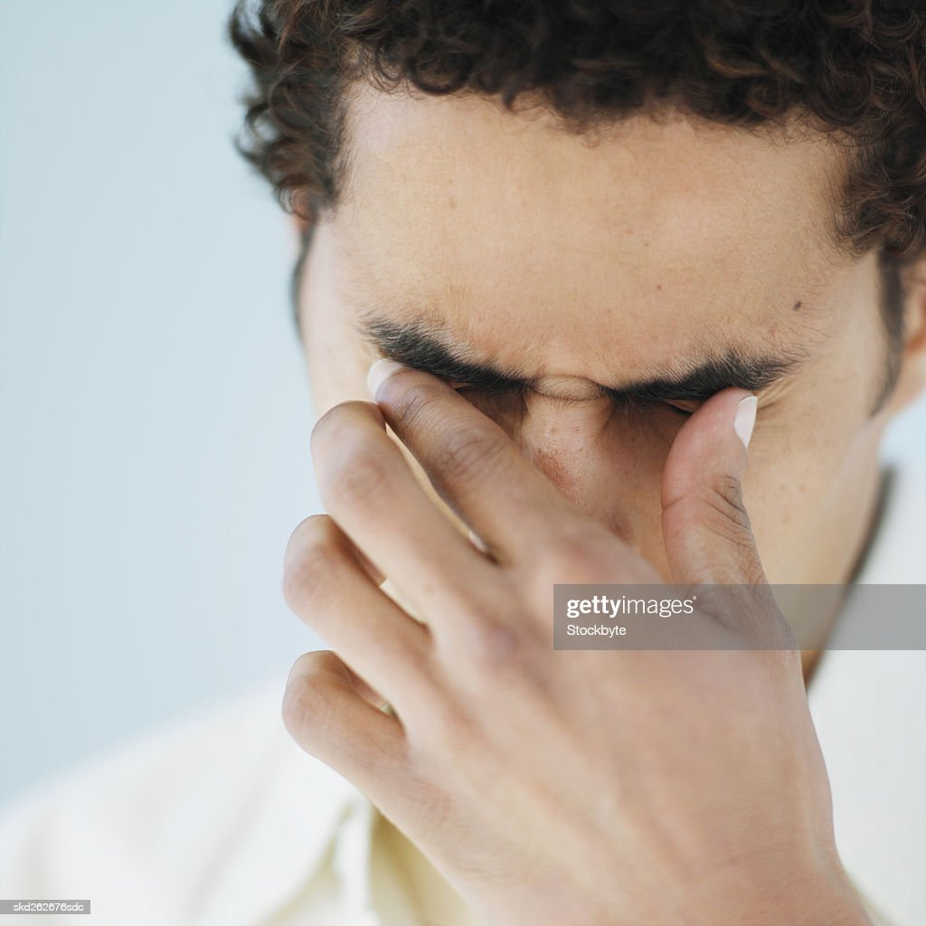 Front view of young man with hand covering face : Stock Photo