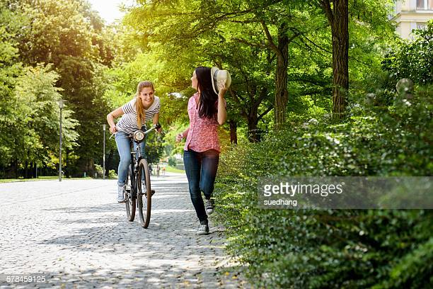 front view of young smiling woman on bicycle chasing young woman holding panama hat - runaway stock pictures, royalty-free photos & images