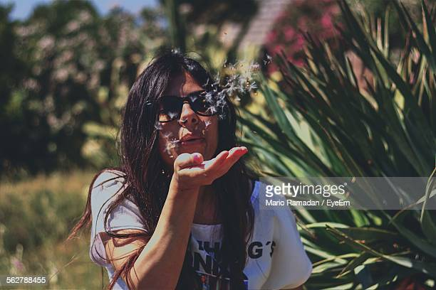 Front View Of Young Woman Blowing Dandelion Seeds Over Palm
