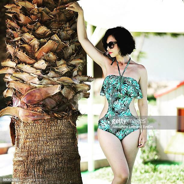 Front View Of Young Woman In Bikini Standing By Tree