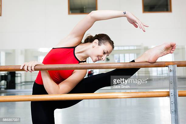 Front view of young woman in dance studio leg raised stretching on barre