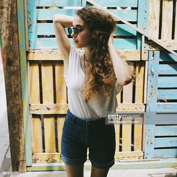 Front View Of Young Woman Standing Against Wooden Wall