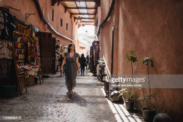 front view of young woman walking in the marrakech souk with a long dress - holy city stock pictures, royalty-free photos & images