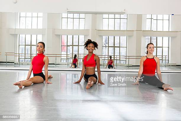 Front view of young women in dance studio side by side doing the splits