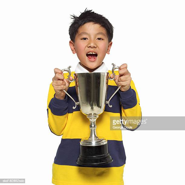 front view portrait of a boy (10-11) holding a trophy