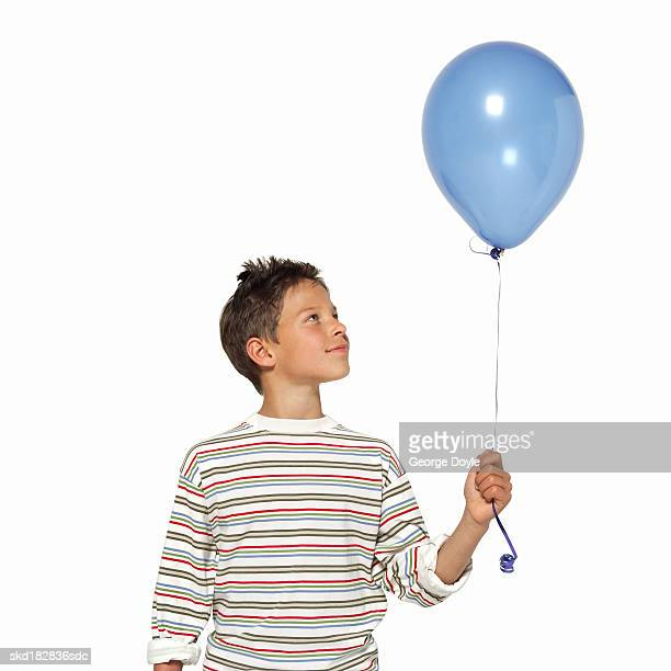 front view portrait of a boy (11-12) holding balloon